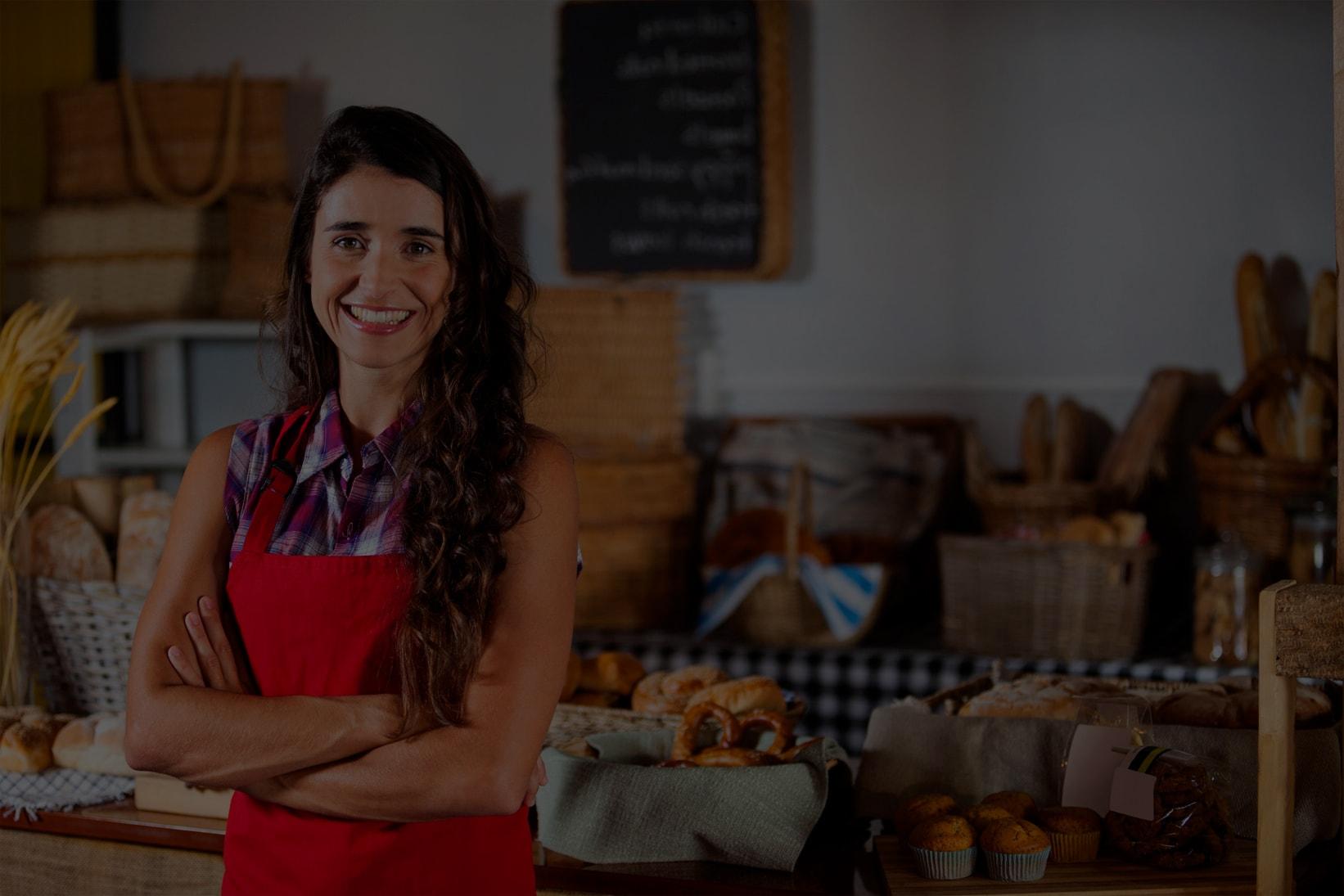mujer atendiendo negocio de panaderia